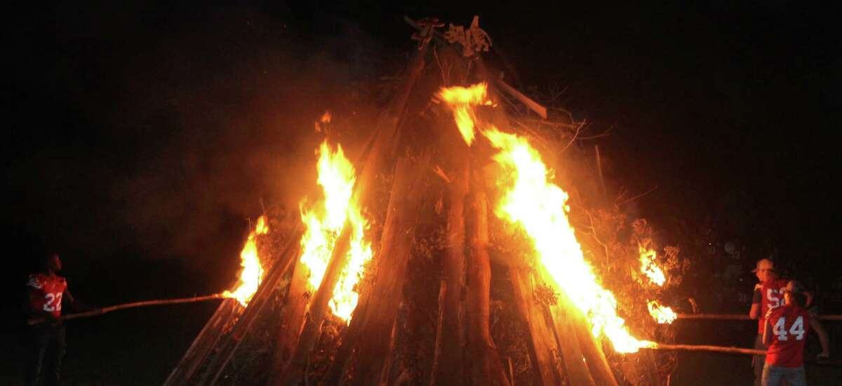The Coldspring-Oakhurst Trojans prepare to light a bonfire in preparation for their homecoming game on the following night.