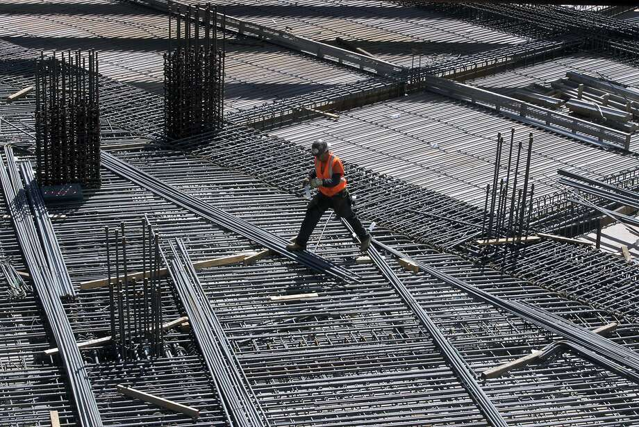 A construction worker walks across a network of rebar on the second level of the Transbay Transit Center project in San Francisco, Calif. on Tuesday, Sept. 23, 2014. Photo: Paul Chinn, The Chronicle