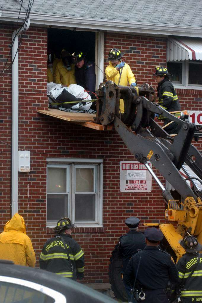 Firefighters Work To Remove The Body Of Alexandros Martakis From His Second Story Apartment On Kent