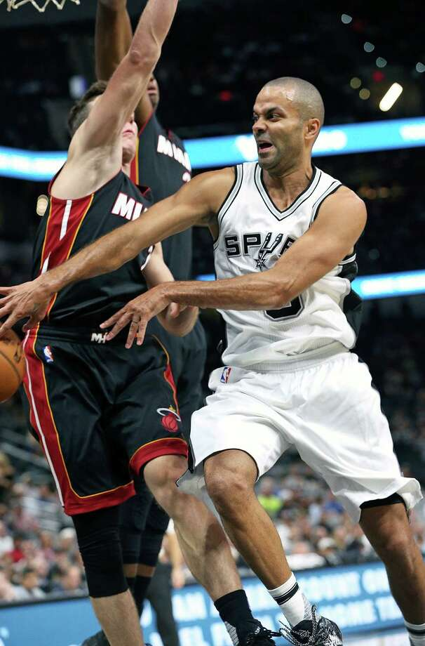 Tony Parker takes two defenders to the hoop and then passes out to the wing as the Spurs host Miami at the AT&T Center on October 14, 2016. Photo: TOM REEL, SAN ANTONIO EXPRESS-NEWS / 2016 SAN ANTONIO EXPRESS-NEWS