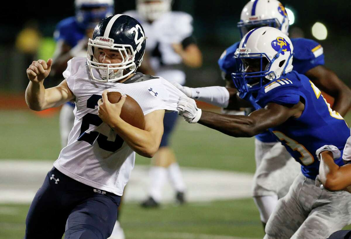 Smithson Valley's Indiana Hawes (23) attempts to evade the grasp of Clemen's Luke Kelley (right) during their game at Lehnhoff Stadium on Friday, Oct. 14, 2016.