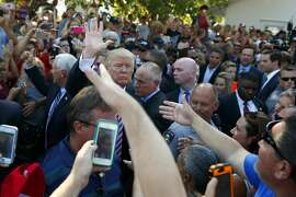 Republican presidential candidate Donald Trump, center left, shakes hands during a visit to the Canfield Fair, Monday, Sept. 5, 2016, in Canfield, Ohio. (AP Photo/Evan Vucci)