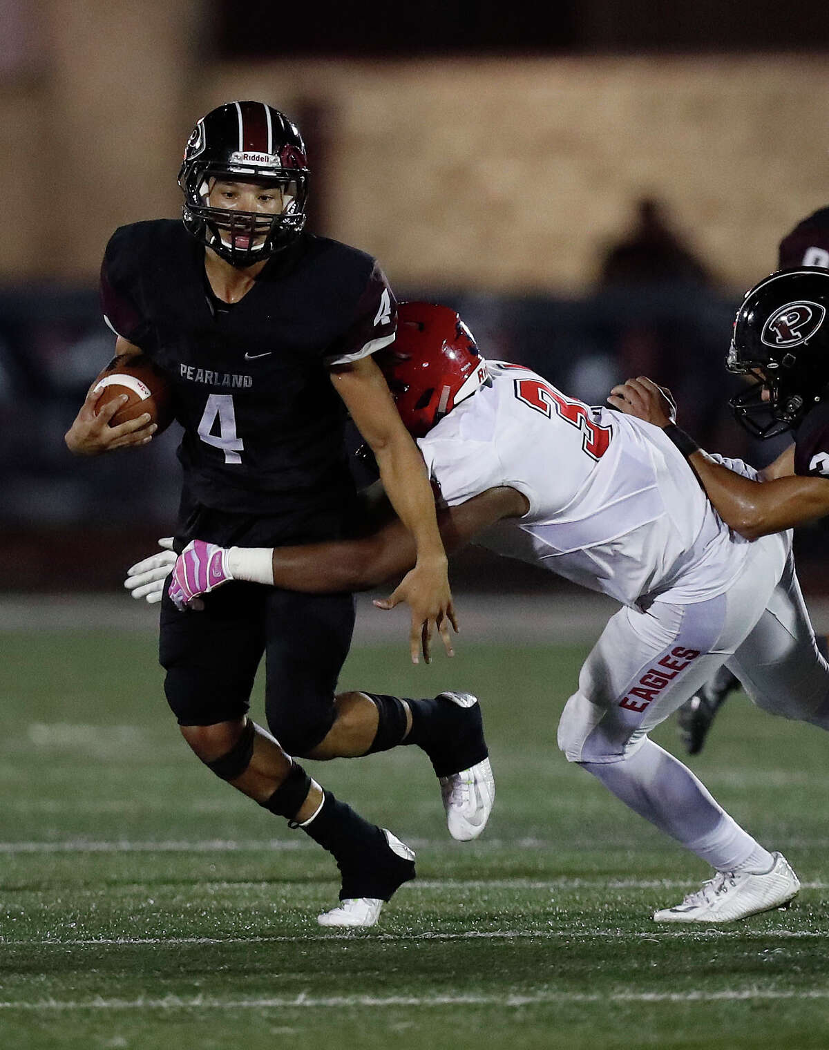 Pearland's running back Davier Pinkston (4) tries to gain yardage on Dawson's Dominque Taylor (34) during the second half of a District 23-6A high school game between Pearland and Dawson, Friday,Oct. 14, 2016 in Pearland.