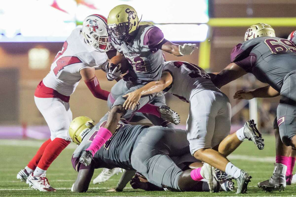 Summer Creek running back Myles Wanza (22) hurdles over the line-of-scrimmage and carries the ball for a first down in a high school football game at Turner Stadium on Friday, October 14, 2016, in Humble.