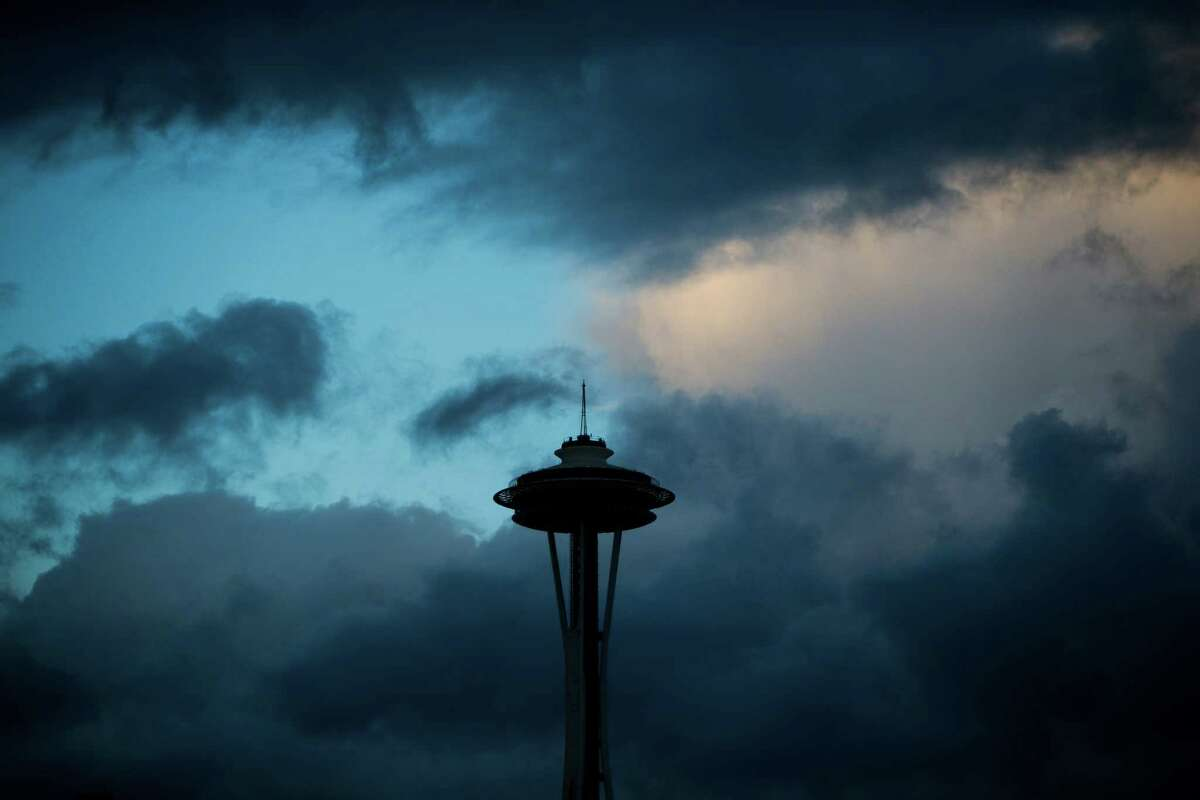 Clear skies and orange sunset light behind the Space Needle as storms move in, Friday, Oct. 14, 2016.