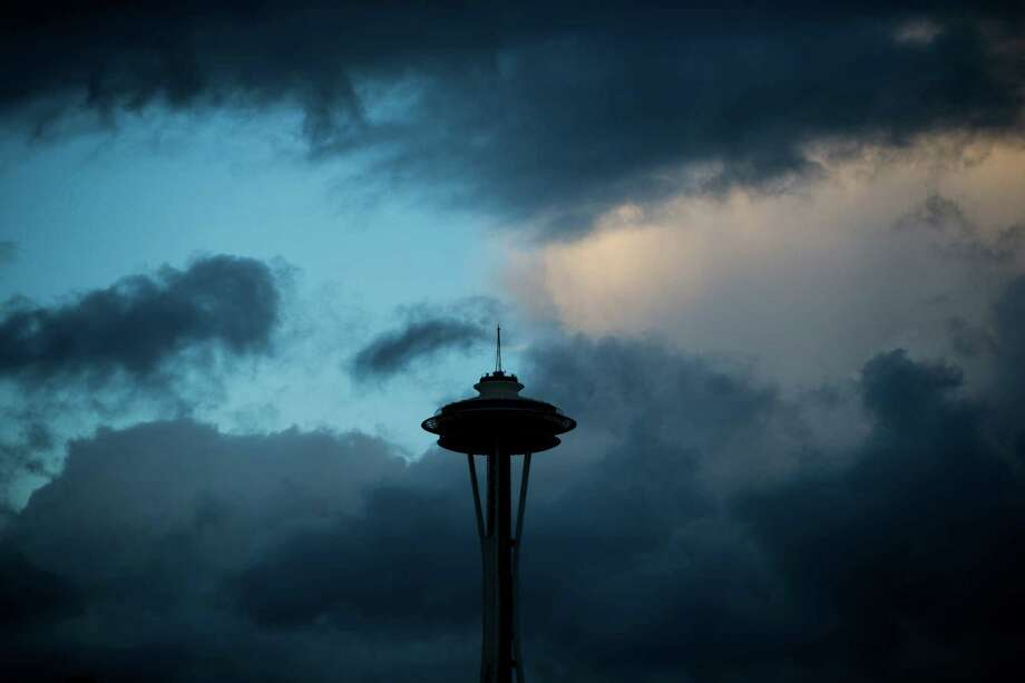 Clear skies and orange sunset light peaks out behind the Space Needle as storms move in for a weekend of weather, Friday, Oct. 14, 2016. Photo: GRANT HINDSLEY, SEATTLEPI.COM / SEATTLEPI.COM