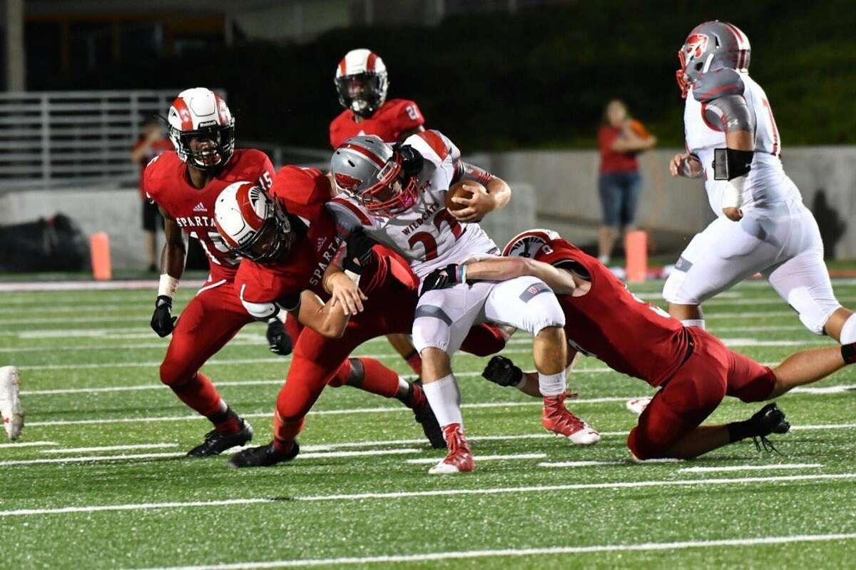 A gang of Porter tacklers take down Splendora fullback Gordon Moore on Friday at Texan Drive Stadium.