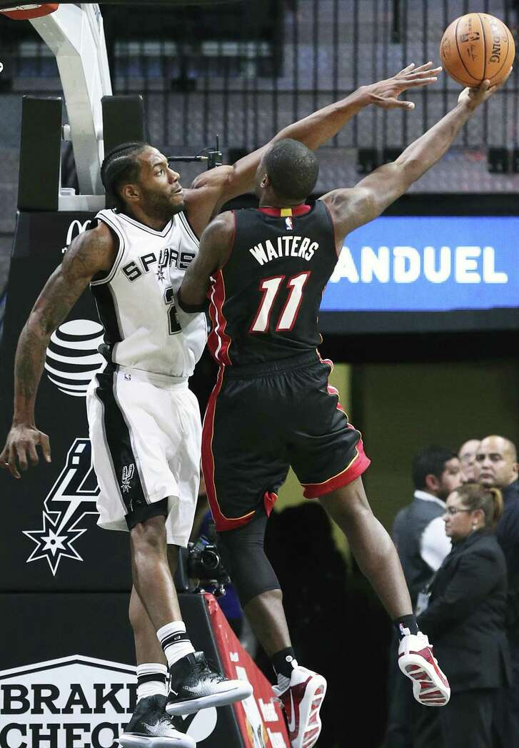 Kawhi Leonard uses his long reach to make a shot difficult for Dion Waiters as the Spurs host Miami in a preseason game at the AT&T Center on Oct. 14, 2016.
