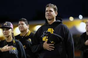 Michigan's football head coach Jim Harbaugh stands for th National Anthem as the Antioch Panthers get set to take on the Liberty Lions in high school football action in Antioch, California, on Friday October 14, 2016