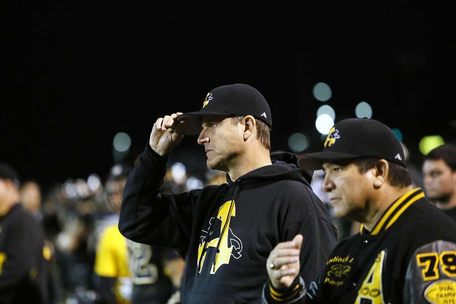 Michigan head coach Jim Harbaugh stands on the sideline with Antioch school principal Louie Rocha (right) on Friday night. Photo: Michael Macor, The Chronicle