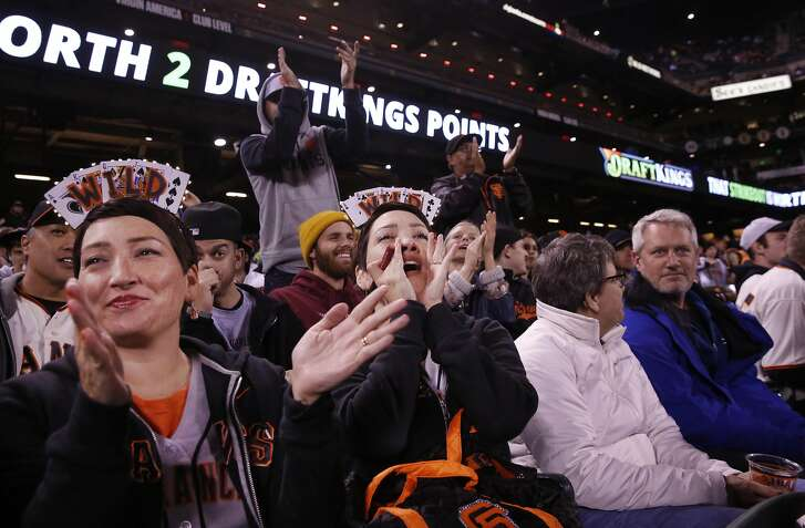 Kristin Hembree, 38, left, and Lisa Thomas, 38, cheer during a Giants game against the Rockies Sept. 28, 2016 in San Francisco, Calif. The twins have been going almost monthly to Giants games since 2011 when their father helped to get them hooked on the sport. Over time, they began making matching headbands to wear and they now do it for every game they go to.