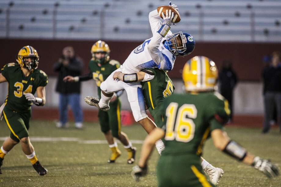 Carman-Ainsworth High School sophomore Dewayne Gurley makes the catch for a first down while being defended by Dow High School senior Jaik Bovee in a game at Midland Stadium on Friday. Photo: Theophil Syslo