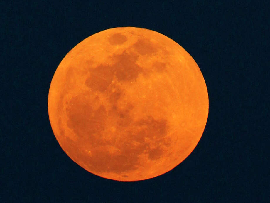 Look up into the sky this weekend - especially Saturday night - and you'll see a bright Supermoon that will appear about 30 percent larger. Earthsky.com says the size difference of year's largest and smallest full moons is comparable to that of a U.S. quarter and a U.S. nickel. The month's full moon is called the Hunter's Moon. Photo: Wilfredo Lee / Associated Press / AP