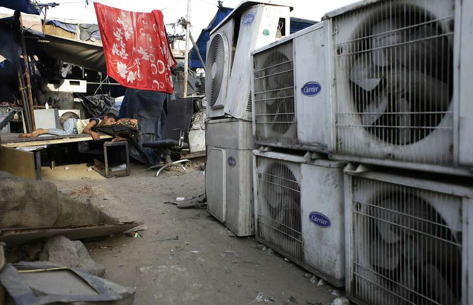 FILE - In this Tuesday, May 17, 2016 file photo, an Indian boy of a migrant daily wageworker sleeps in scorching summer temperatures near an air conditioner shop at a marketplace in New Delhi, India. Nations reached a deal Saturday, Oct. 15, 2016 to limit the use of hydrofluorocarbons, or HFCs - greenhouse gases far more powerful than carbon dioxide that are used in air conditioners and refrigerators, in a major effort to fight climate change. (AP Photo/Altaf Qadri, File) Photo: Altaf Qadri, Associated Press
