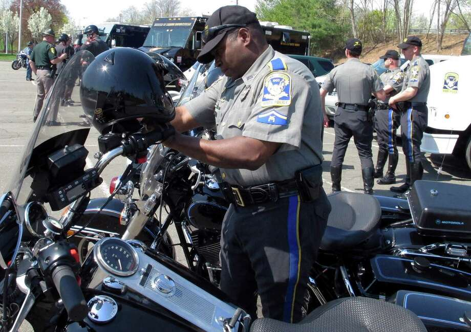 Connecticut Trooper Walter Greene straps his helmet onto his motorcycle prior to a news conference in Windsor, Connecticut, on Monday, May 4, 2015. Troopers in all six New England states launched the region's first coordinated crackdown on speeding and failing to wear seat belts. (AP Photo/Dave Collins) Photo: Dave Collins / Associated Press / AP