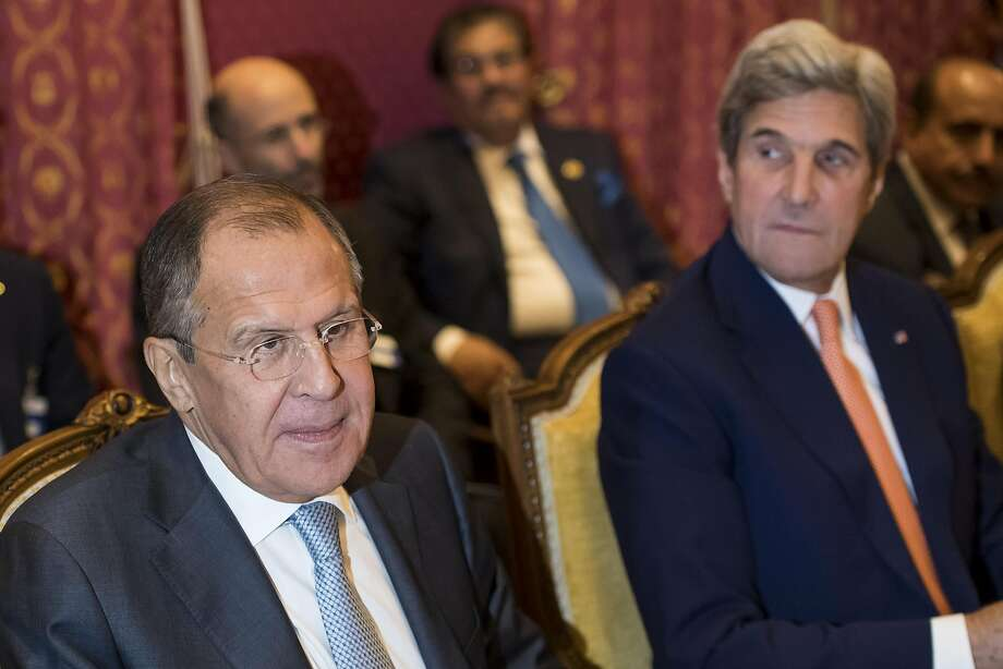 Russian Foreign Minister Sergey Lavrov (left) confers with U.S. Secretary of State John Kerry. Photo: Jean-Christophe Bott, Associated Press