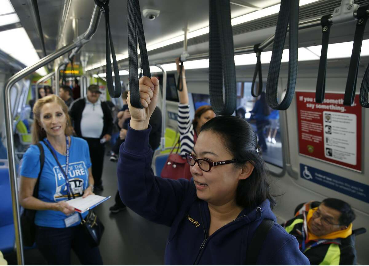 Sandra Jeong holds the longer handle straps aboard the new BART train cars during an open house tour at the Pleasant Hill station in Pleasant Hill, Calif. on Saturday, Oct. 15, 2016.