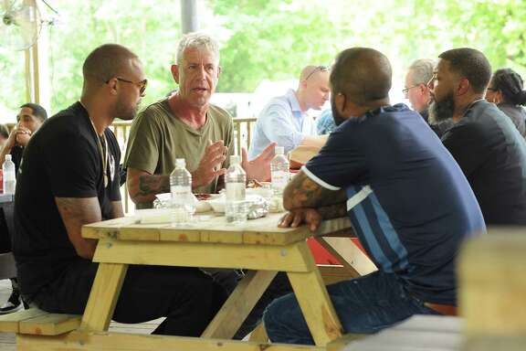 """Parts Unknown"" host Anthony Bourdain, second from left, is filmed at Burns Original BBQ in June. Bourdain last featured the barbecue joint on an episode of his previous show in 2003."