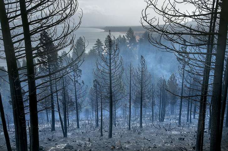 Lake Tahoe can be seen behind the Emerald Fire along Highway 89,  Friday, Oct. 14, 2016 near Lake Tahoe, Nev. A wind-whipped wildfire raged out of control Friday in northern Nevada, destroying more than a dozen homes, forcing evacuations, closing roads and schools, and triggering power outages, officials said. (Randall Benton/The Sacramento Bee via AP)