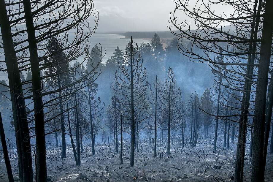Lake Tahoe can be seen behind the Emerald Fire along Highway 89,  Friday, Oct. 14, 2016 near Lake Tahoe, Nev. A wind-whipped wildfire raged out of control Friday in northern Nevada, destroying more than a dozen homes, forcing evacuations, closing roads and schools, and triggering power outages, officials said. Photo: Randall Benton, Associated Press