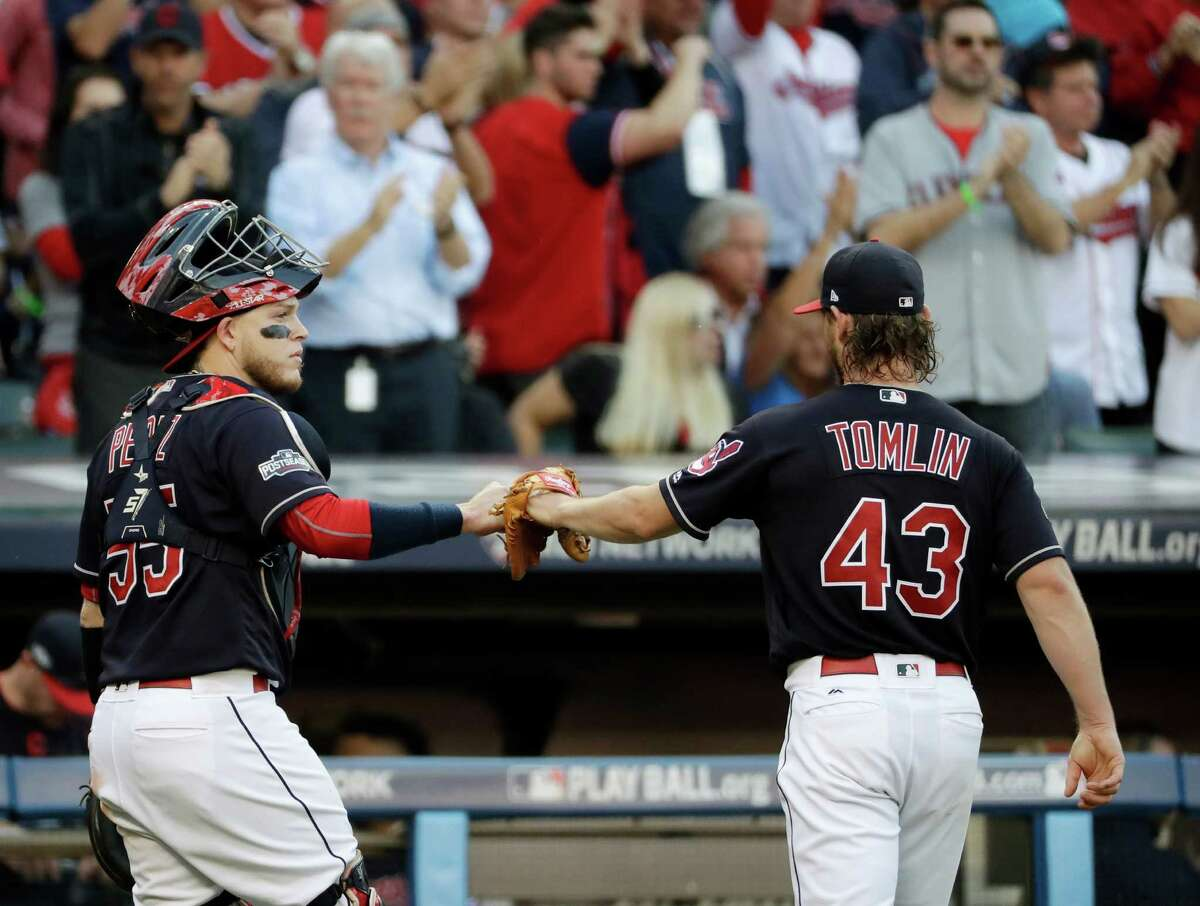 Cleveland Indians catcher Roberto Perez, left, and starting pitcher Josh Tomlin celebrate as they leave the field during the fifth inning in Game 2 of baseball's American League Championship Series in Cleveland, Saturday, Oct. 15, 2016.