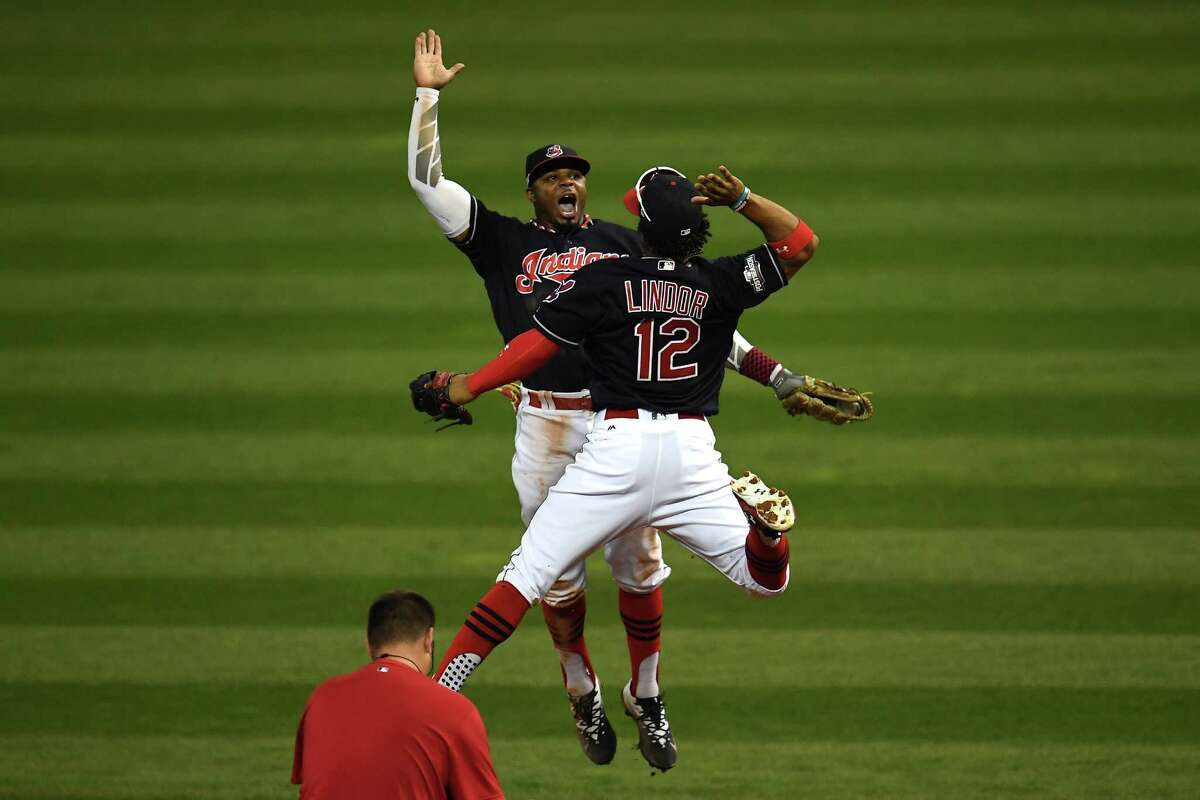 CLEVELAND, OH - OCTOBER 15: Francisco Lindor #12 and Rajai Davis #20 of the Cleveland Indians celebrate after defeating the Toronto Blue Jays with a score of 2 to 1 in game two of the American League Championship Series at Progressive Field on October 15, 2016 in Cleveland, Ohio.