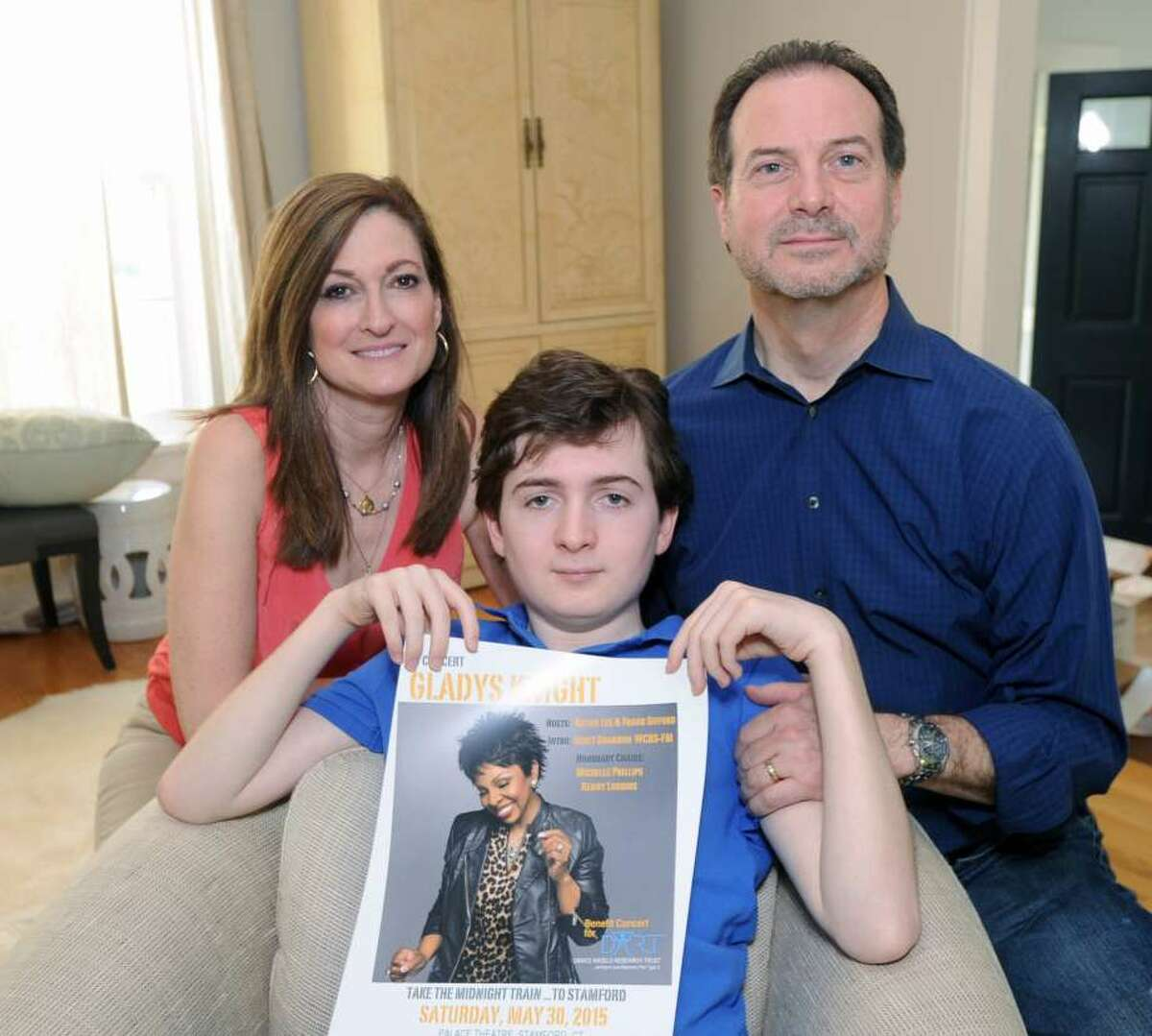 Phil and Andrea Marella with their son, Andrew Marella, now 17, hold up a poster for a benefit concernt last year.
