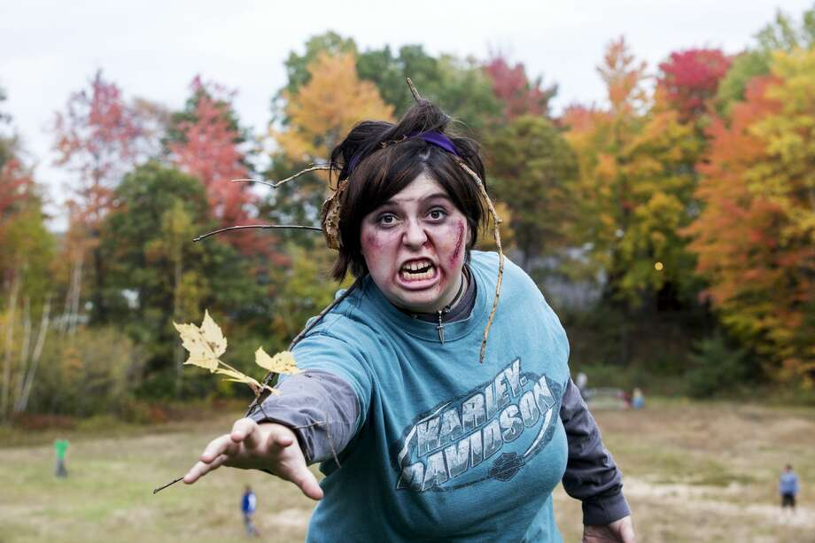 THEOPHIL SYSLO | For the Daily News Jessie Mathewson, 17, of Midland, acts as a zombie while participating in the last obstacle at the Zombie Run (5K) at City Forest on Saturday. Photo: THEOPHIL SYSLO | For The Daily News