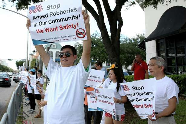 Zhang Lu Zheng, left, hoists a poster during a Saturday protest against rising crime in the Chinatown neighborhood and businesses. The protesters gathered at Westheimer and Post Oak to vent their concerns.