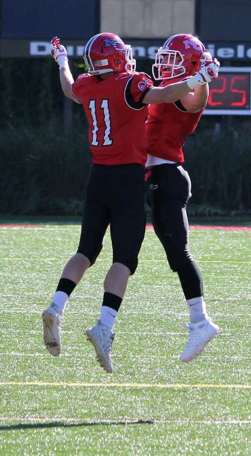New Canaan's Jack Hoelzer (11) and Ryan O'Connell celebrate after Hoelzer's second quarter touchdown. Photo: Anthony E. Parelli / Hearst Connecticut Media / New Canaan News
