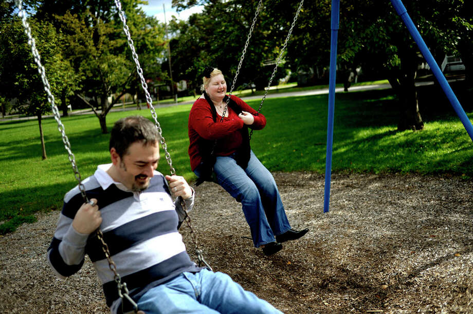 NICK KING | nking@mdn.net  Artist Heather Deogracia, right, closes her eyes while swinging with her boyfriend Matt Dexter last weekend at Grove Park in Midland. / Midland Daily News