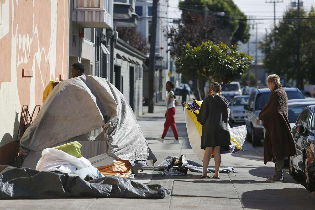 People along Shotwelll street stand next to tents on the sidewalk on Wednesday, September 28, 2016 in San Francisco, California.