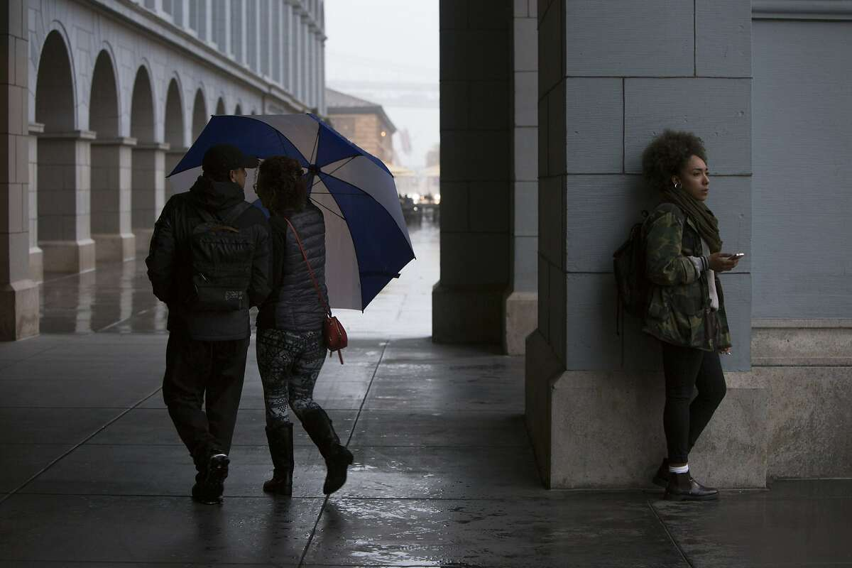 Mia Felder of Chinatown takes shelter from a sudden rain storm under the Ferry Building on Saturday, Oct. 15, 2016 in Oakland.