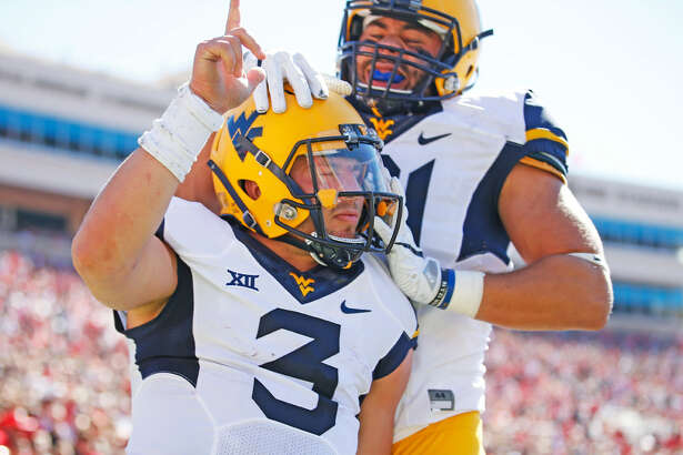 West Virginia's Skyler Howard (3) celebrates with Trevon Wesco (81) after scoring a touchdown against Texas Tech during an NCAA college football game, Saturday, Oct. 15, 2016, in Lubbock, Texas. (Brad Tollefson/Lubbock Avalanche-Journal via AP)