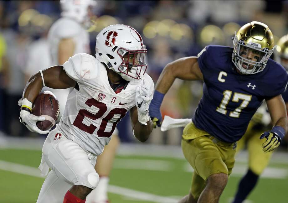 Stanford running back Bryce Love (20) runs around Notre Dame linebacker James Onwualu (17) during the second quarter of an NCAA college football game in South Bend, Ind., Saturday, Oct. 15, 2016.  Photo: Michael Conroy, Associated Press