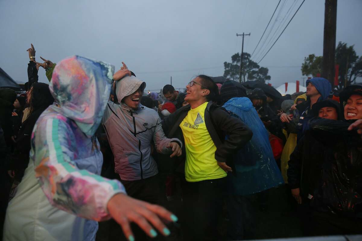 Kristopher Williams, center left, dances with others during a downpour as Kamaiyah performs during first day of the Treasure Island music festival Oct. 15, 2016 in San Francisco, Calif.
