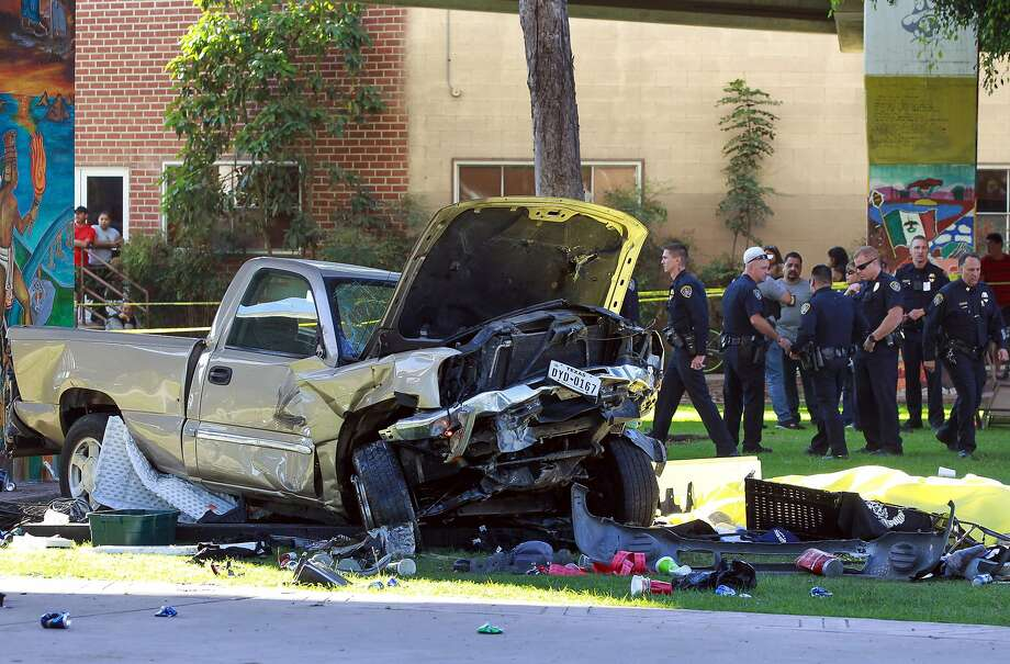 Police stand near the pickup truck that landed at Chicano Park after it flew off a ramp to the San Diego Coronado Bridge in San Diego on Saturday, Oct. 15, 2016.  Four people were killed and nine were injured on Saturday after an out-of-control pickup truck plunged off the San Diego-Coronado Bridge and plowed into crowd gathered at a festival below, authorities said.   (Hayne Palmour IV/The San Diego Union-Tribune via AP) Photo: Hayne Palmour IV, Associated Press
