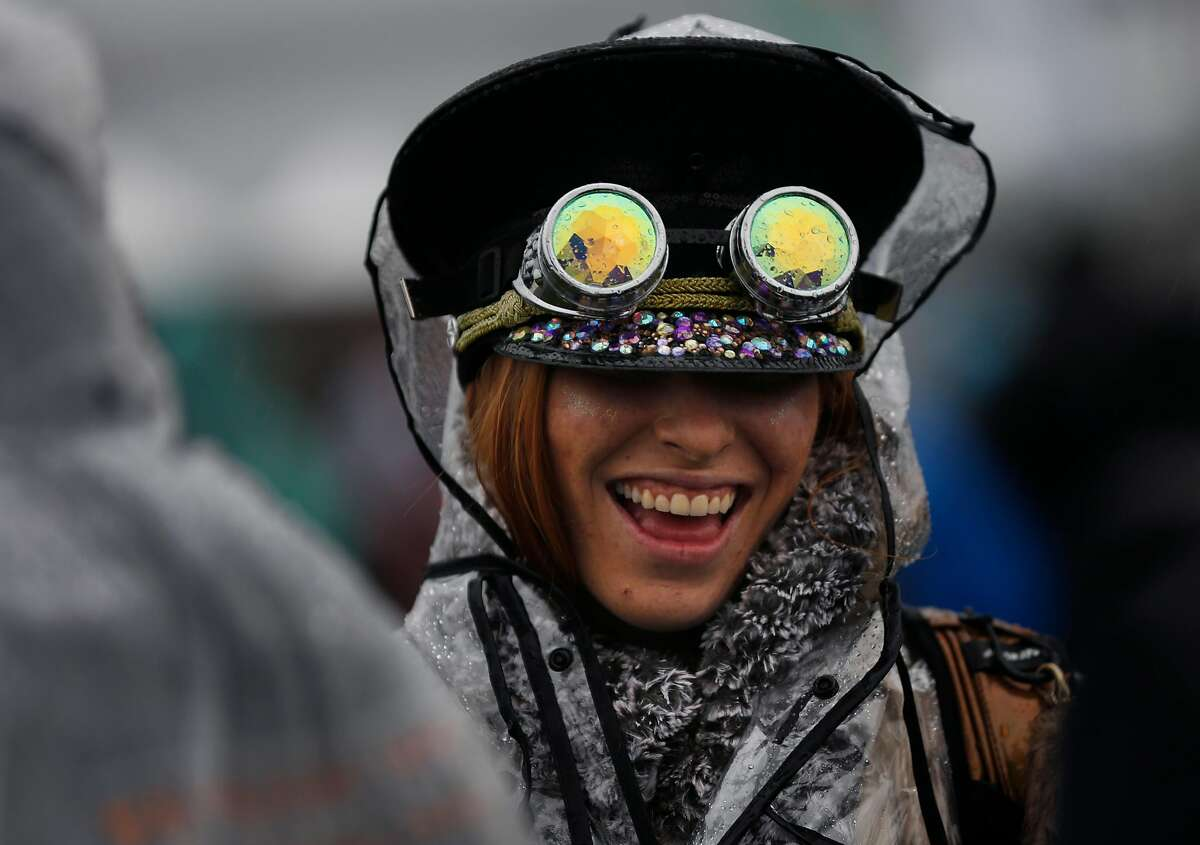 Taylor Gompper jokes with friends as rain pours down during first day of the Treasure Island music festival Oct. 15, 2016 in San Francisco, Calif.