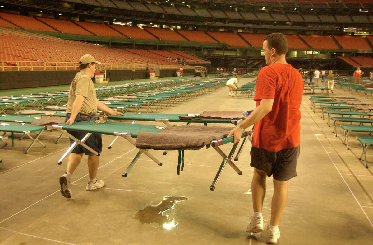Red Cross volunteers set up cots for refugees of Hurricane Katrina arriving by bus from the SuperDome to the Astrodome on Aug. 31, 2005. (Chronicle/Carlos Rios) .