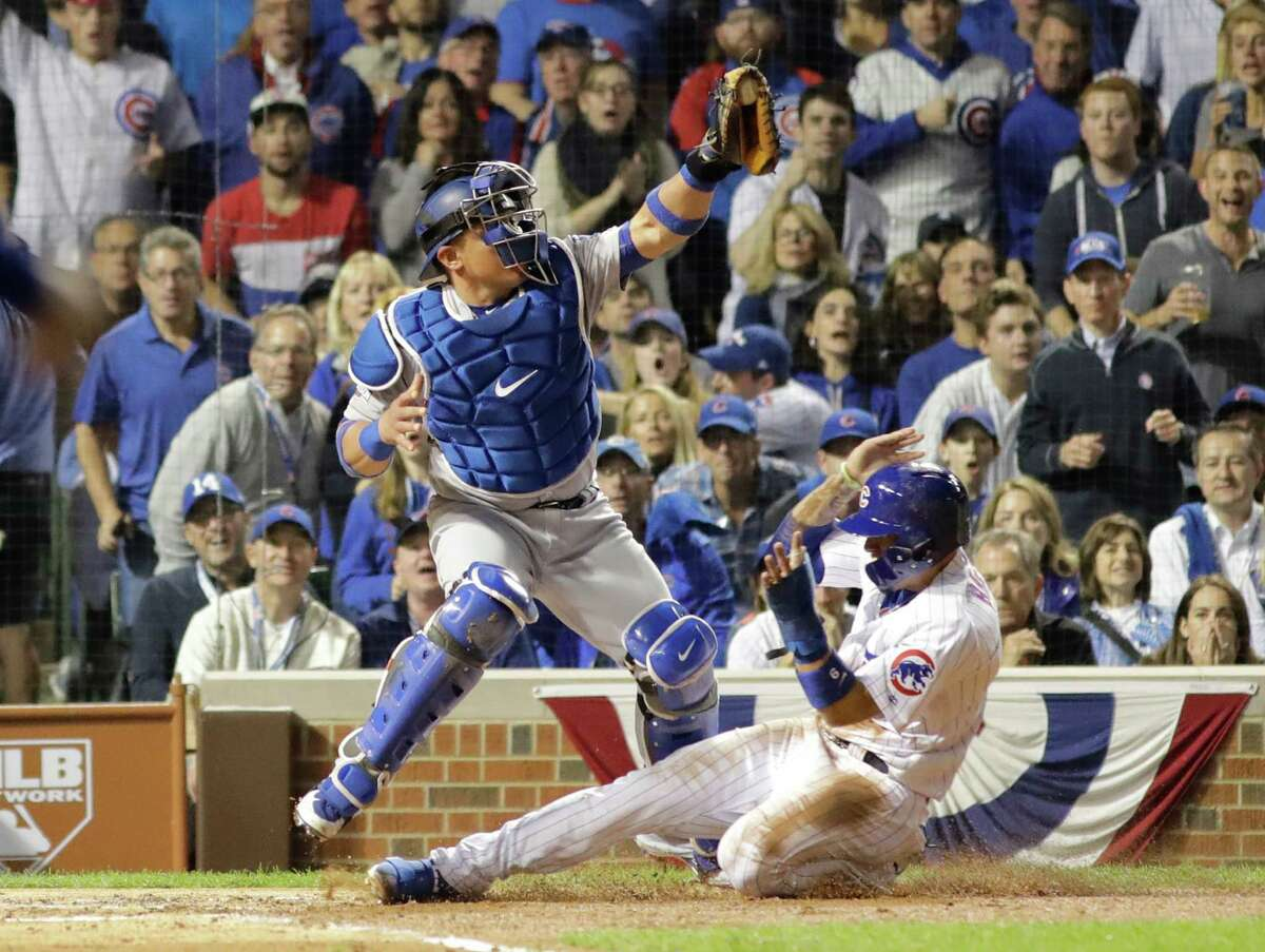 Chicago Cubs' Javier Baez (9) steals home against Los Angeles Dodgers catcher Carlos Ruiz (51) during the second inning of Game 1 of the National League baseball championship series Saturday, Oct. 15, 2016, in Chicago.