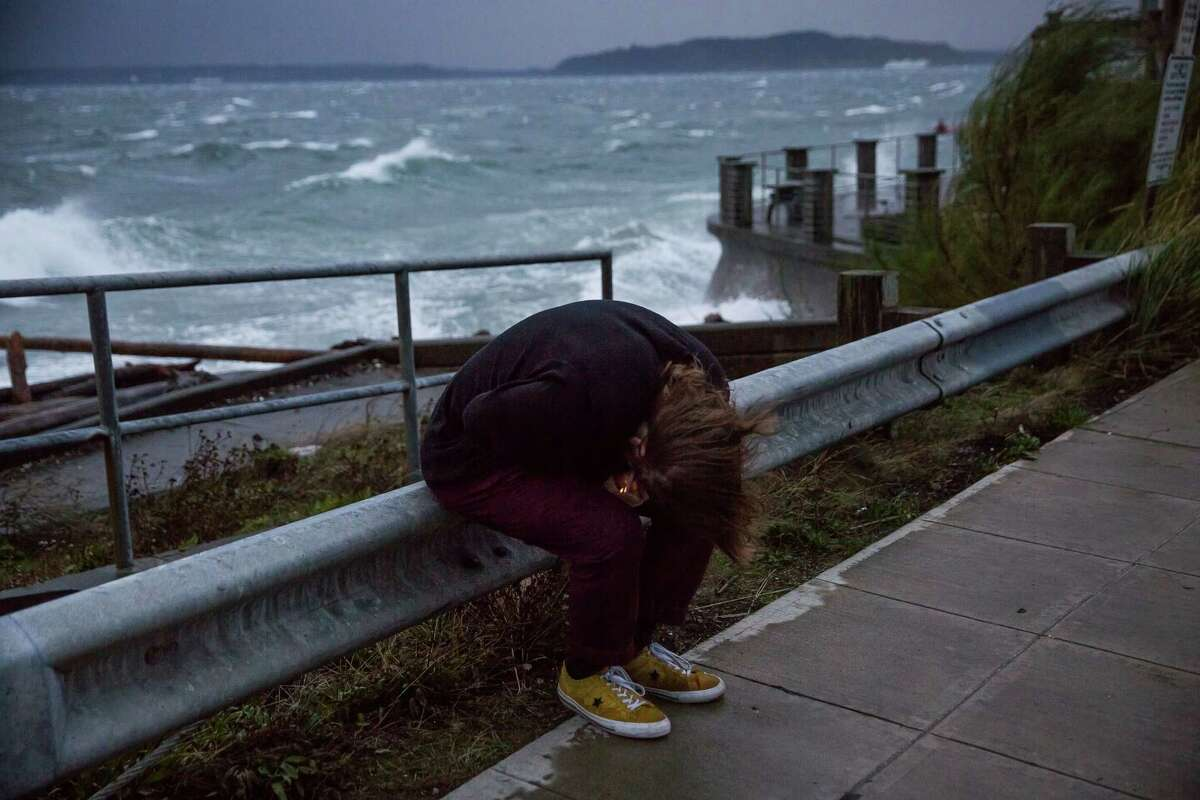 A man huddles to light a cigarette at Charles Richey Sr. Viewpoint in West Seattle as the remnants of Typhoon Songda hit Western Washington on Saturday evening, Oct. 15, 2016.