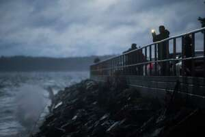 Thrill seekers stand on Charles Richey Sr. Viewpoint in West Seattle as the remnants of Typhoon Songda hit Western Washington on Saturday evening, Oct. 15, 2016.