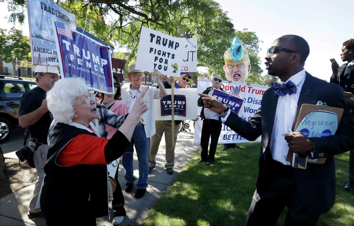 Minister Martez Thompson, right, a supporter of Democratic presidential candidate Hillary Clinton goes up against supporters for Republican presidential candidate Donald Trump outside a campaign stop by Clinton at Wayne State University, Monday, Oct. 10, 2016, in Detroit. (AP Photo/Carlos Osorio)