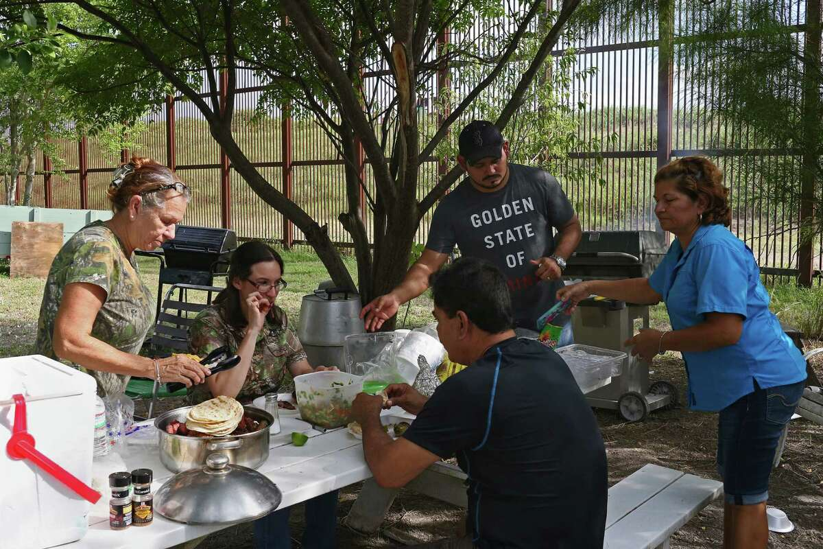 """In La Lomita neighborhood of Brownsville, Texas, the Granados family grills in their backyard, Sunday, Oct. 2, 2016. The neighborhood is next to the U.S.-Mexico border wall and serves as a backdrop to the family's Dallas Cowboys game-watch cookouts. The younger Edgar Granados said, ?'You can build anything, they?•ll still get through.?"""" The family has witness immigrants scale the wall in under a minute."""