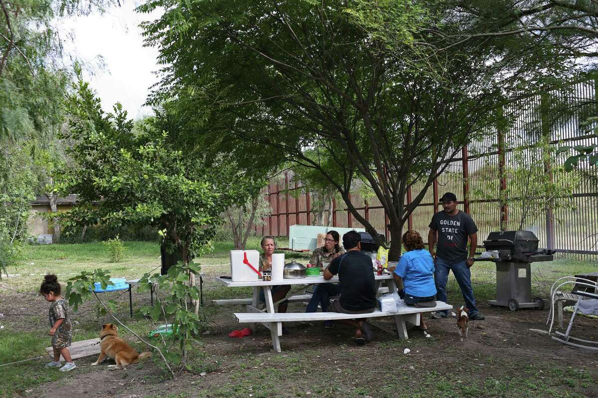 Members of the Grandos family grill in their backyard next to the border barrier in Brownsville. They've seen migrants scale the fencelike wall in less than a minute.