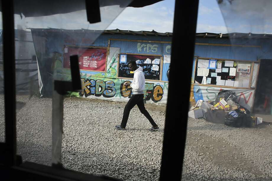 A man passes the Kids Cafe in a refugee camp near Calais, France. The camp is to close by year's end. Photo: Thibault Camus, Associated Press