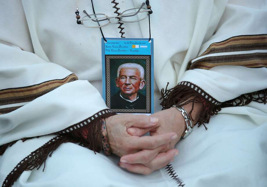 A woman wears an image of Jose Gabriel del Rosario Brochero during a vigil where the priest once lived in Villa Cura Brochero in the mountainous Argentine province of Cordoba. Photo: NICOLAS AGUILERA, AFP/Getty Images