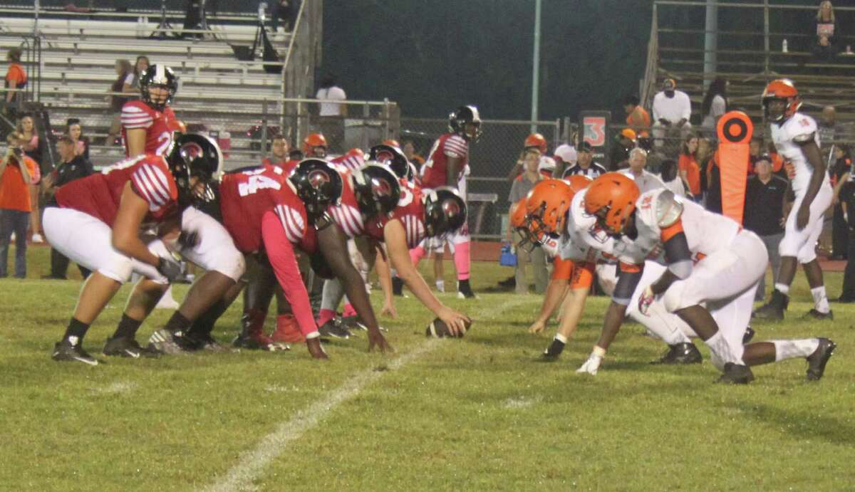 The Coldspring-Oakhurst Trojans (left) prepare to play offense against the Trinity Tigers.