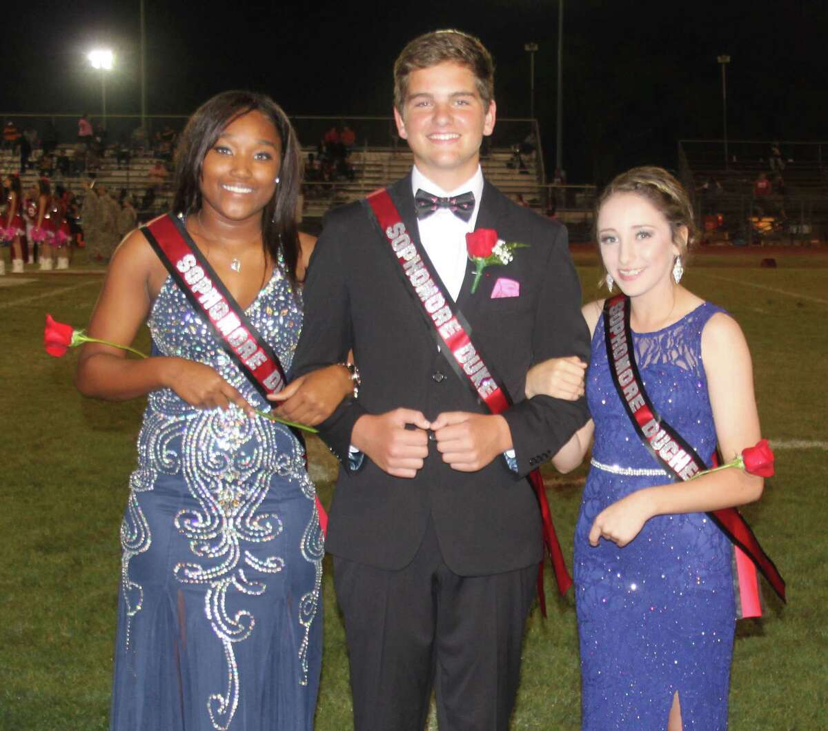 Coldspring-Oakhurst High School Sophomore Duke Brendan Beard (middle) escorts Duchesses Rylee Rudloff (right) and Acheanna Norman (left) during the Trojanhomecoming game on Oct. 14 against the Trinity Tigers.