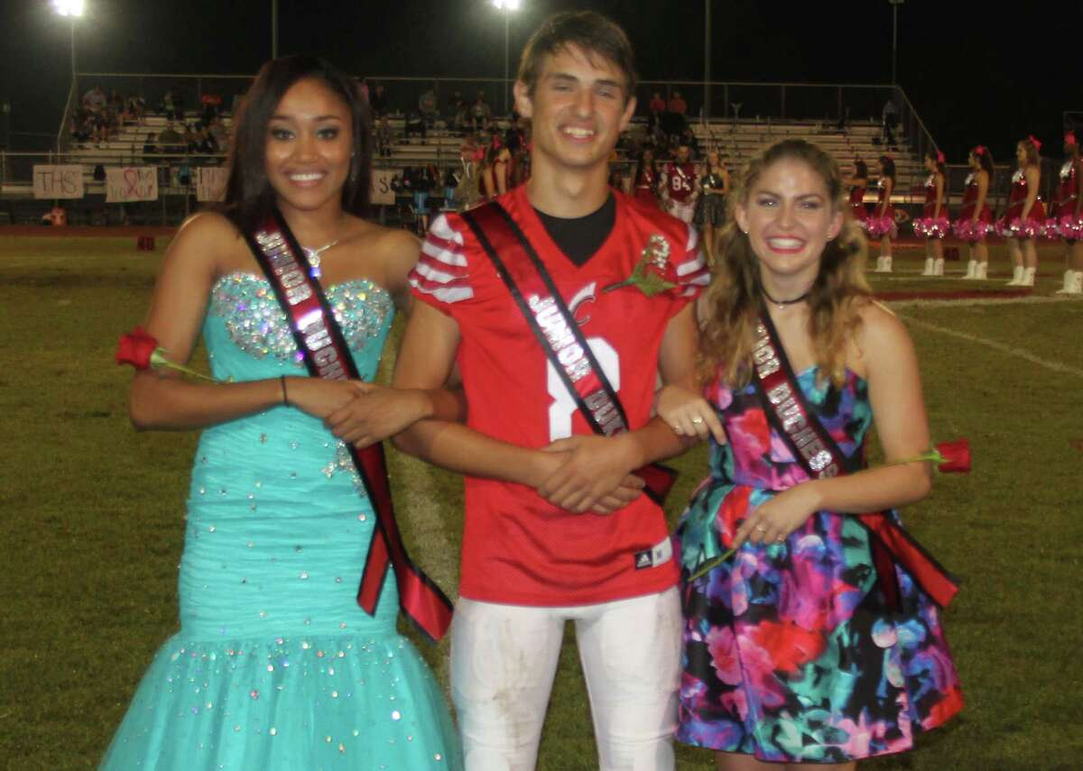 Junior Duke Jack Patrick (middle) stands to the side of the field with Junior Duchesses Nautica Norman (left) and Rachel Duwel (right).